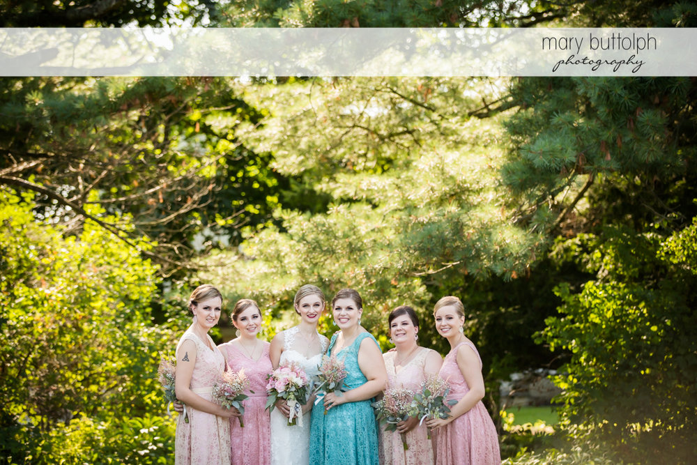 Bride and her bridesmaids with flowers in the garden at John Joseph Inn and Elizabeth Restaurant Wedding