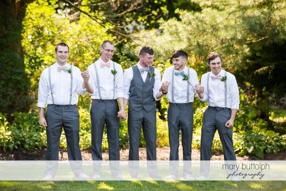 Groom and groomsmen hold hands in the garden at John Joseph Inn and Elizabeth Restaurant Wedding