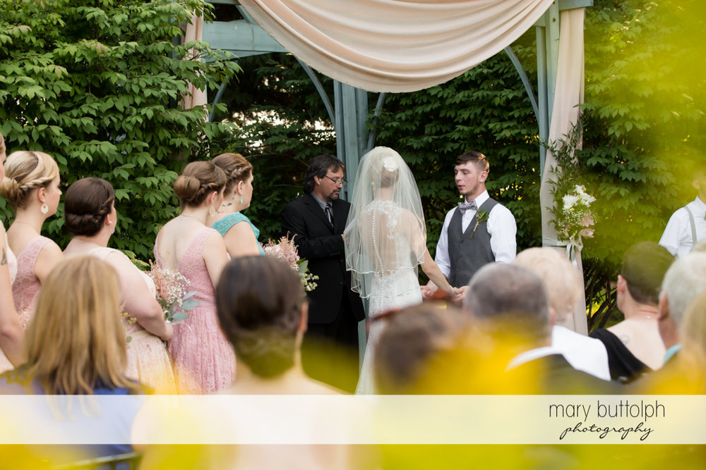 Couple get married in the garden as guests look on at John Joseph Inn and Elizabeth Restaurant Wedding