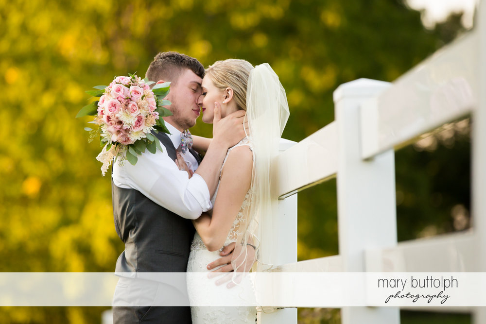 Couple share a tender moment near a wooden fence at John Joseph Inn and Elizabeth Restaurant Wedding