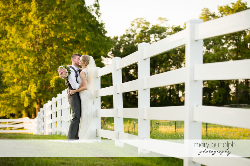 Couple kiss near a wooden fence in the garden at John Joseph Inn and Elizabeth Restaurant Wedding