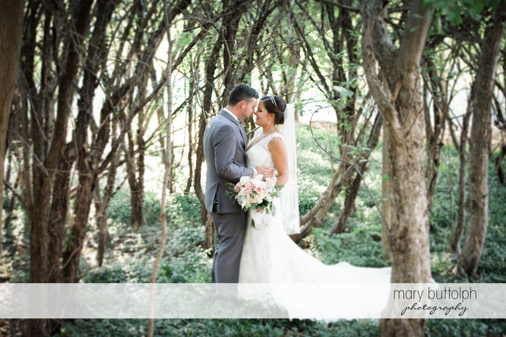 Couple embrace in the woods at The Lodge at Welch Allyn Wedding