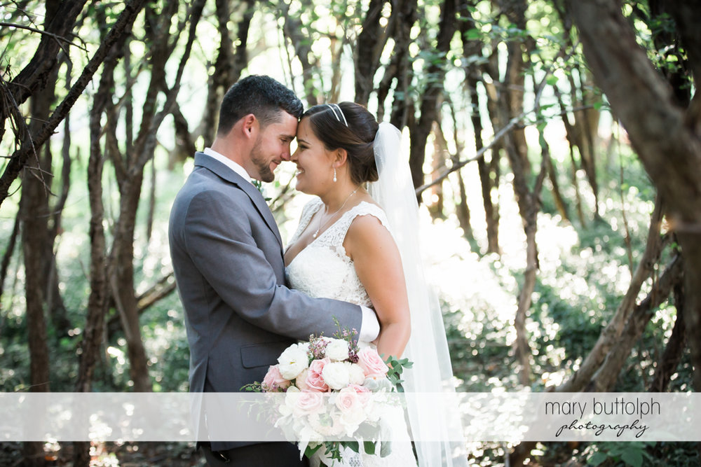 Couple rub noses in the woods at The Lodge at Welch Allyn Wedding