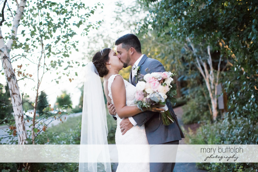 Couple show their affection in the woods at The Lodge at Welch Allyn Wedding