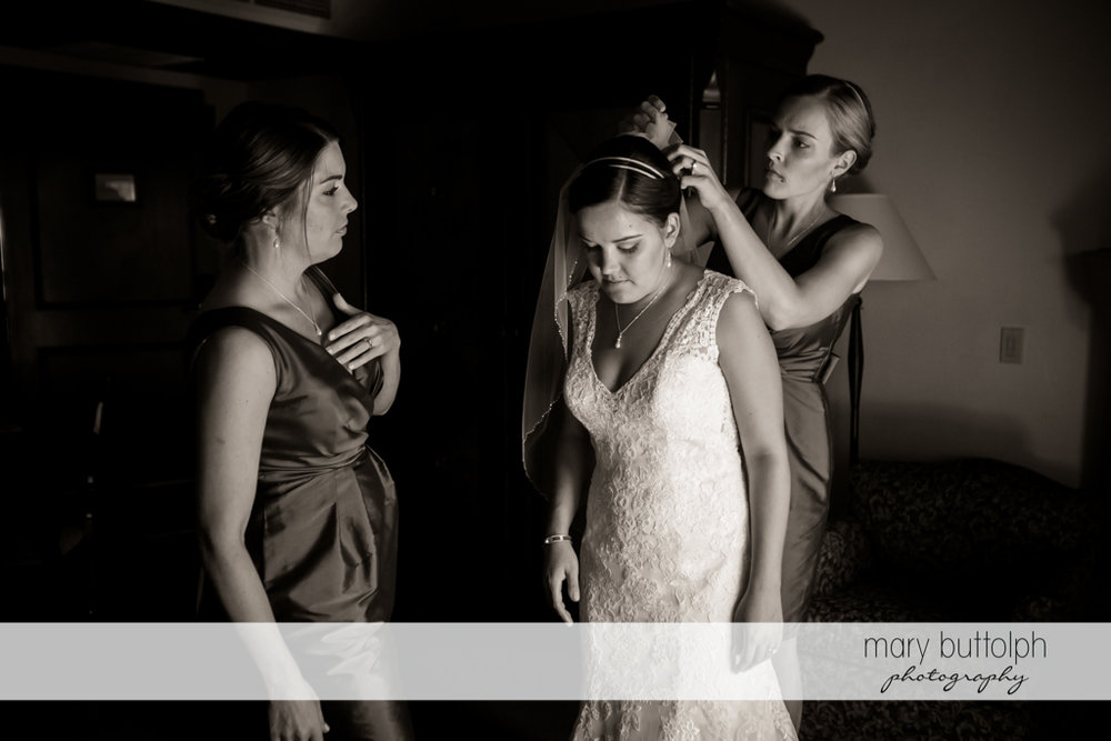 Woman fixes the bride's wedding veil at The Lodge at Welch Allyn Wedding