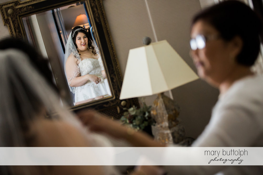 Bride sees herself in the mirror at Aurora Inn Wedding