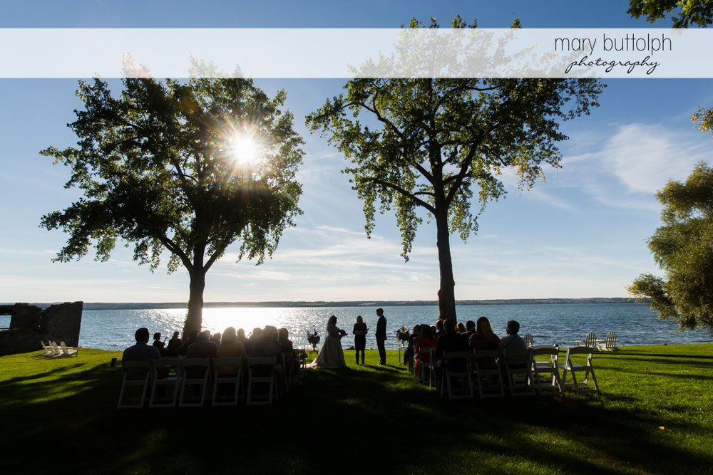 Couple wed near the lake in the sunset at Aurora Inn Wedding
