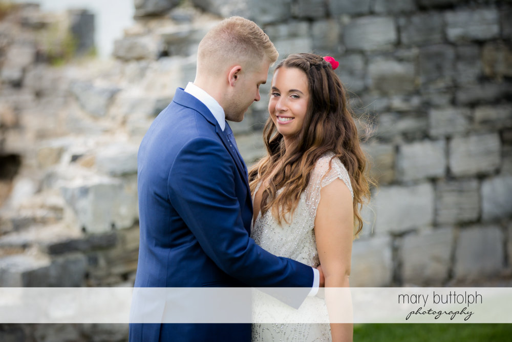 Couple stand in front of a brick wall at Aurora Inn Wedding