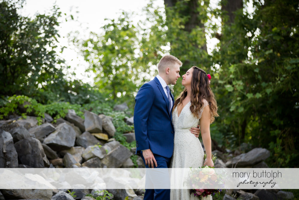 Couple pose in front of rocks in the garden at Aurora Inn Wedding