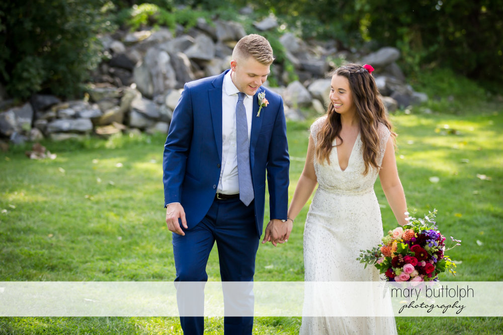 Couple hold hands as they take a quiet stroll in the garden at Aurora Inn Wedding