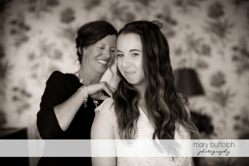 Bride gets some help from her mom in putting on her wedding dress at Aurora Inn Wedding
