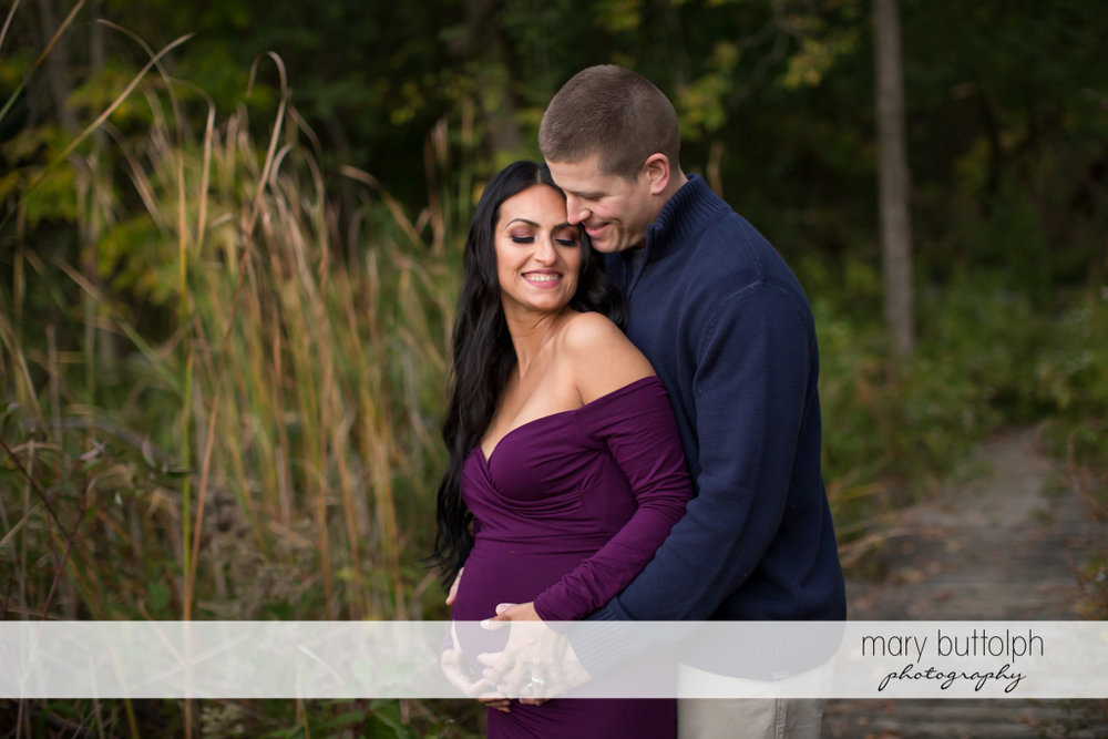 Man and his pregnant wife relax in the woods at Skaneateles Maternity Photography