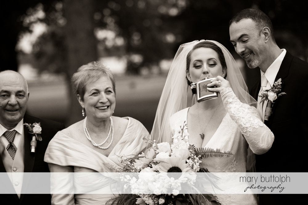 Bride takes a drink from a flask as her parents and the groom look on at Emerson Park Pavilion Wedding