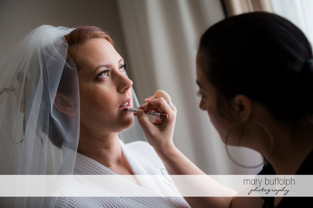 Woman applies lip gloss to the bride at Emerson Park Pavilion Wedding