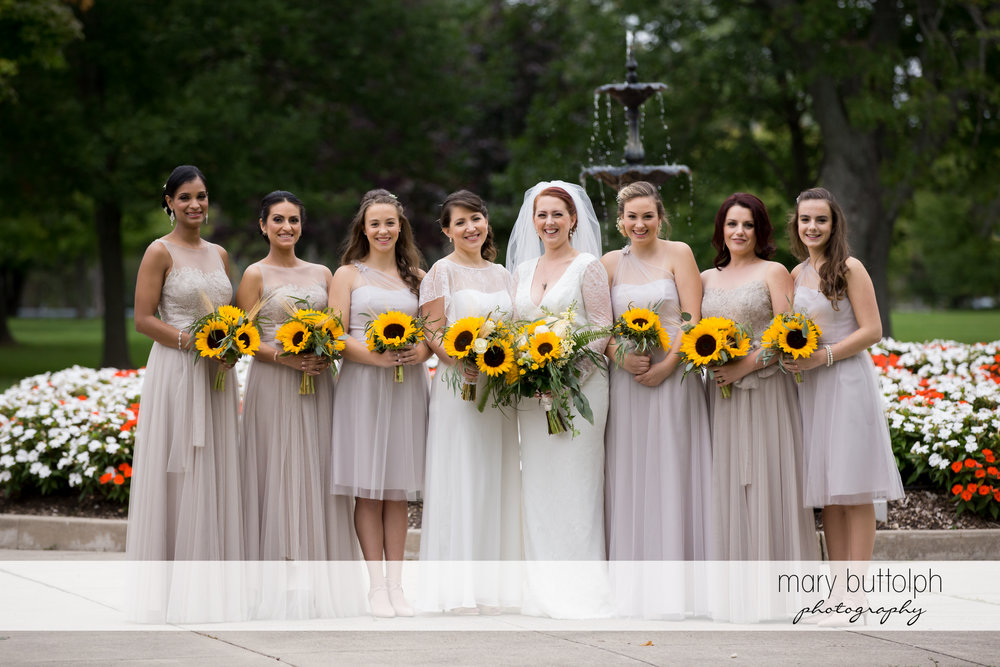 Bride and bridesmaids holding sunflowers in the garden at Emerson Park Pavilion Wedding