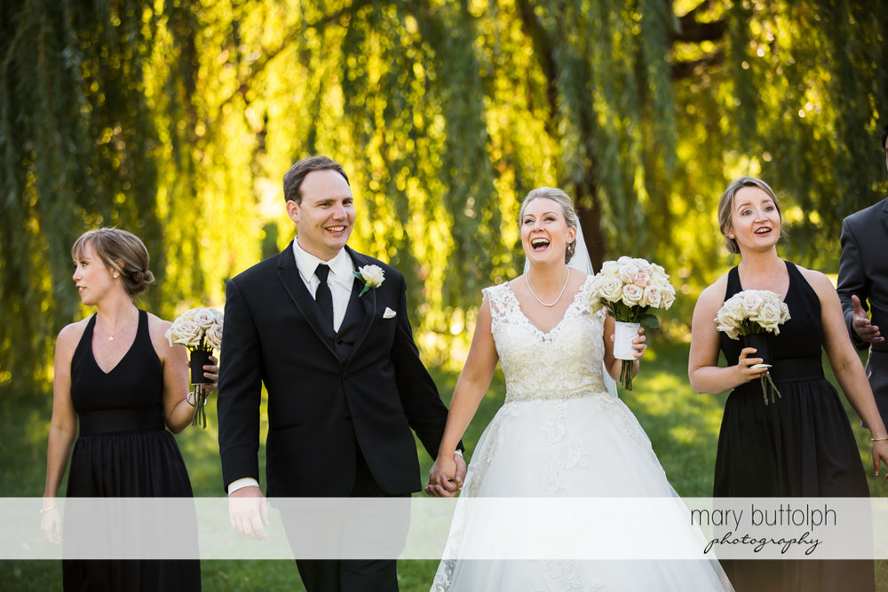 Couple and bridesmaids stroll in the park at SKY Armory Wedding