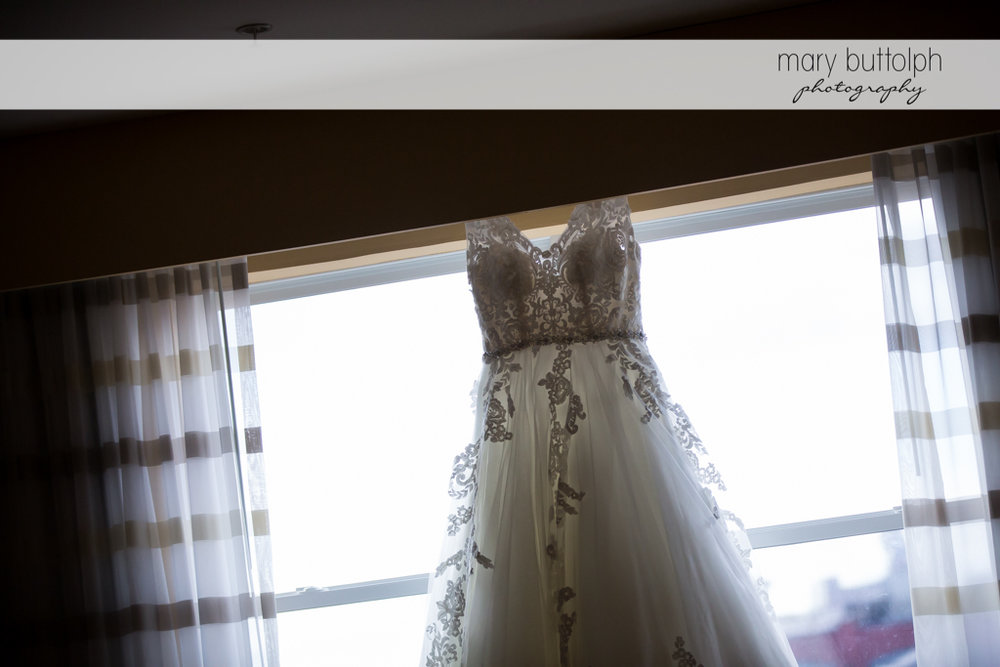 Bride's wedding dress hangs from a window at SKY Armory Wedding