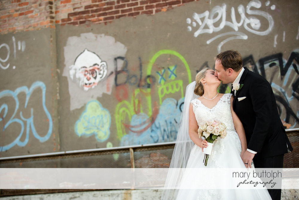 Couple kiss in front of a wall full of graffiti at SKY Armory Wedding