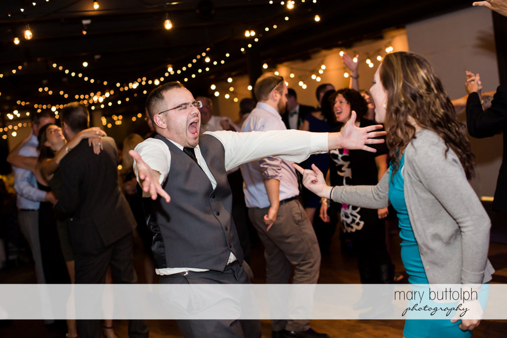 Couple's guests have fun at the wedding reception at SKY Armory Wedding