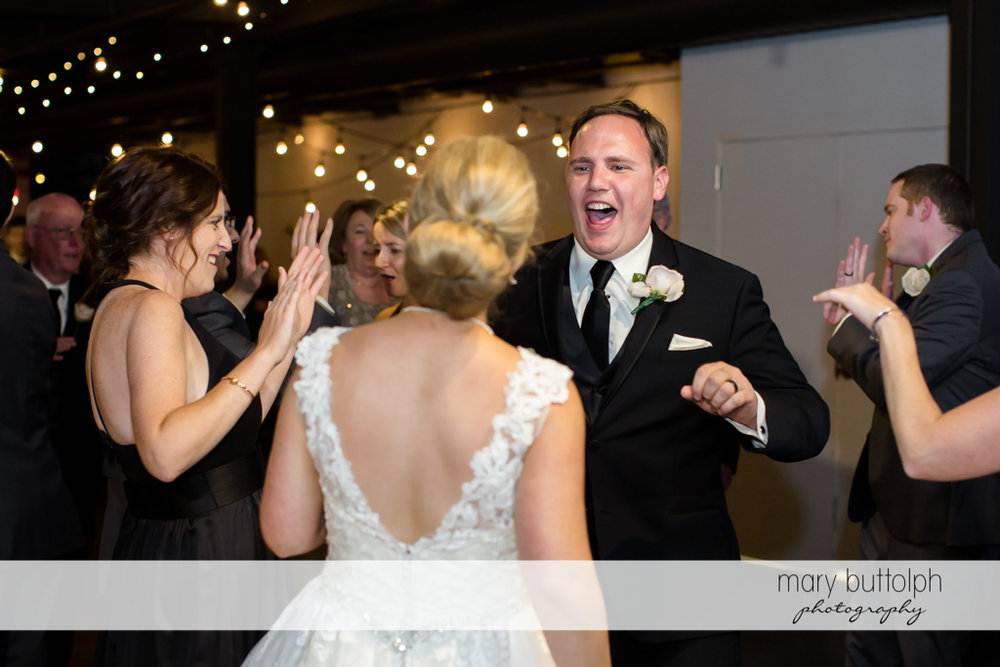Couple in a light moment with guests at SKY Armory Wedding