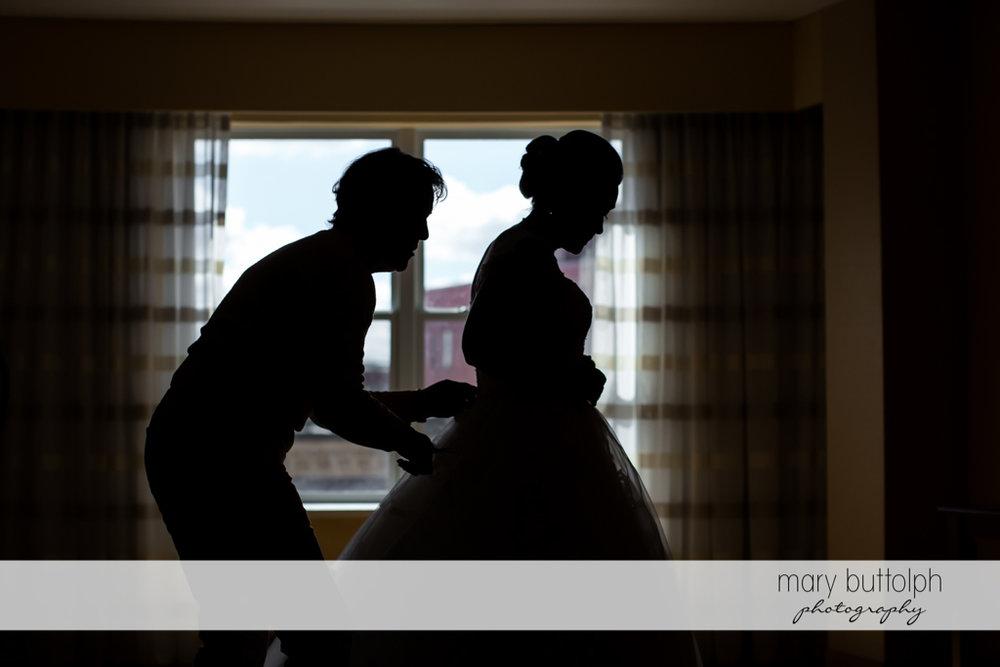 Groom helps bride put on her wedding dress at SKY Armory Wedding
