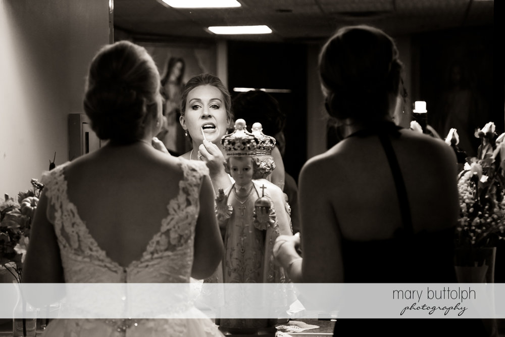 Bride applies lip gloss in front of a small statue of the Baby Jesus at SKY Armory Wedding