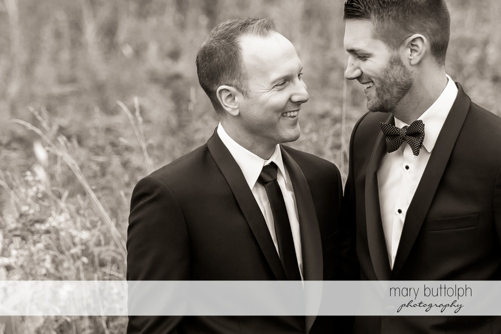 Same sex couple standing in a field at Anyela's Vineyards Wedding