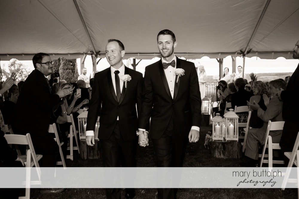 Same sex couple leave the wedding tent while they are applauded by guests at Anyela's Vineyards Wedding