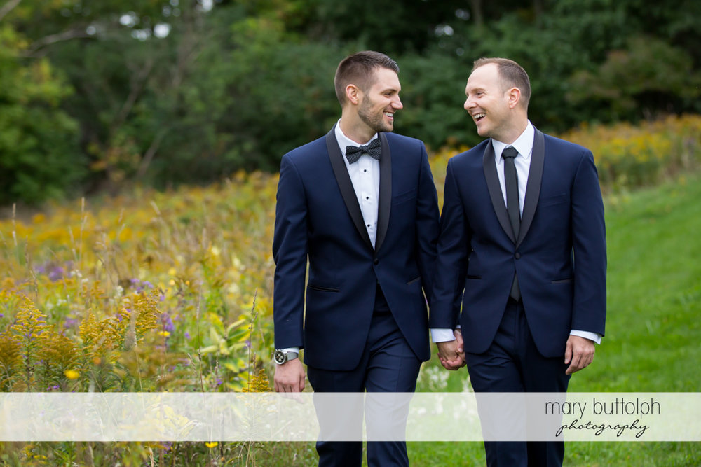 Same sex couple take a stroll in the garden at Anyela's Vineyards Wedding