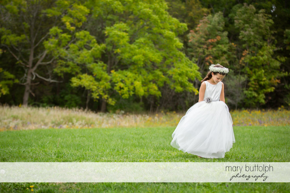 Same sex couple flower girl in front of trees at Anyela's Vineyards Wedding