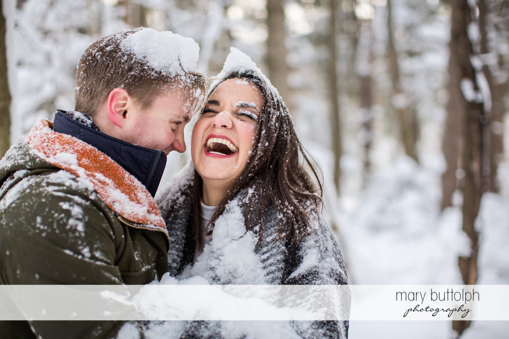 Couple laugh while covered in snow at Highland Forest Engagement