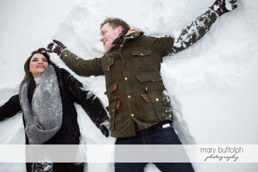 Couple lie in the snow at Highland Forest Engagement