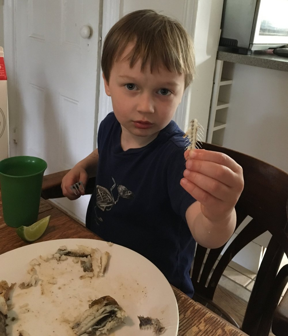 Cash at dinner tonight, showing me the spine of the fish. That's the head on his plate - you can see the head more clearly in the title photo of this post.