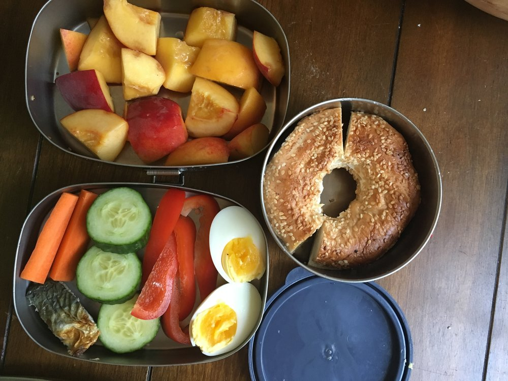Day 4: Snacks in the tiffin-style stacking container (top and bottom L), and main lunch in the round container. Morning snack: raw carrots, cucumbers and peppers, small piece of mackerel, boiled egg. Afternoon snack: cut-up peaches. Lunch: bagel, adjusted as requested to have cream cheese only (no jam).