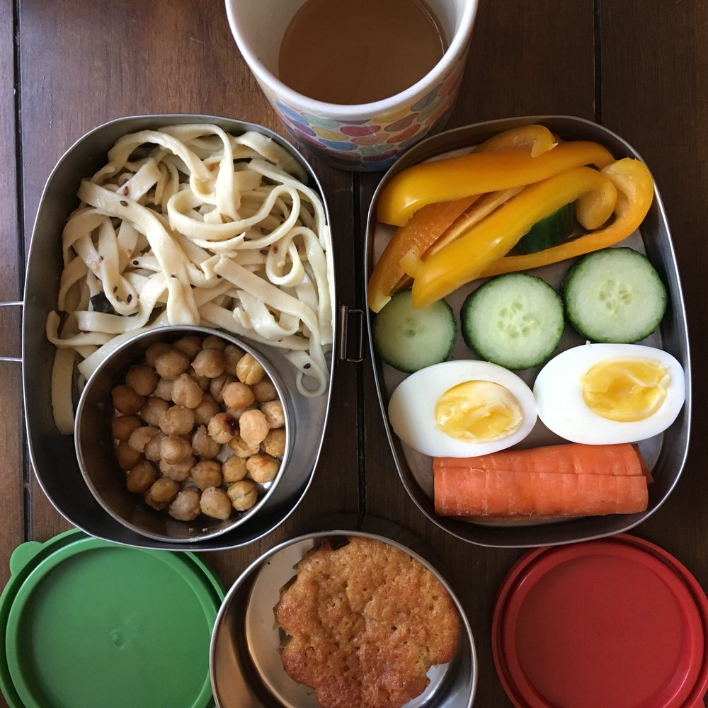 Day 5. On L, for lunch: homemade noodles with sesame seeds and lightly roasted chickpeas; On R, for morning snack: raw peppers, cucumbers, carrot and a boiled egg; below, for afternoon snack: a lemon-honey cake, a special treat for the last day. Top, coffee: an essential tool in the lunch-making parent's arsenal.