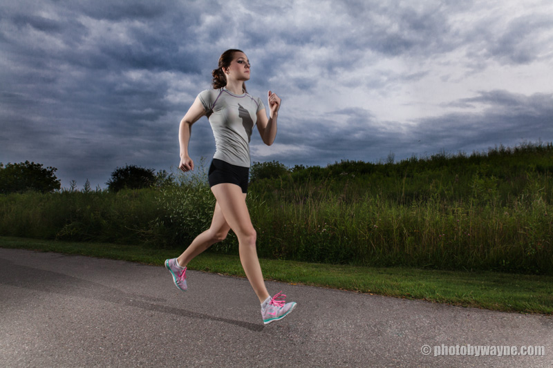 female-fitness-model-running-outdoor-dramatic-cloud