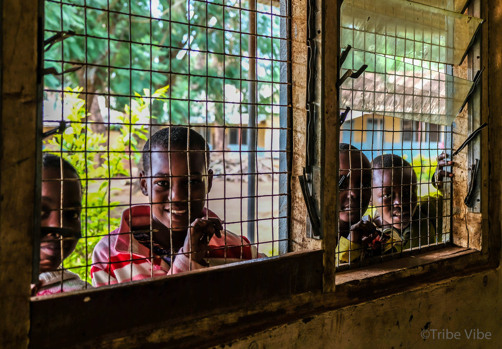 Chaga school boys peering into their classroom through the window.