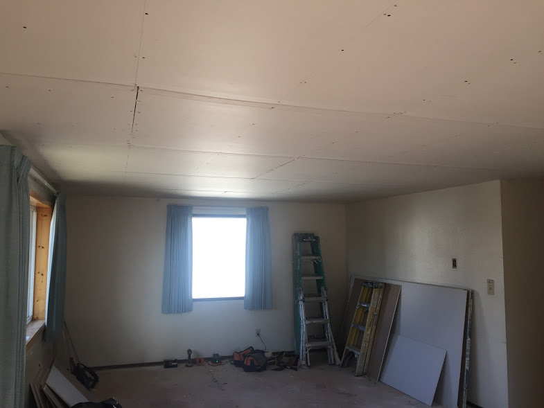 Drywall being installed over textured ceiling. The ceiling texture, commonly used in the past, has absbestos. Nowadays, it's cheaper and easier to simply cover it with another layer of drywall than to demo and dispose of it. Disposal of absbestos is possible to do, but very labor intensive. In Hillsboro, Oregon, one can dispose of it but it must be wrapped and tied and extra thick plastic bags. that are marked as toxic waste. They charge a lot for disposal as well, as they must cover the large bags with 2ft of dirt every night.