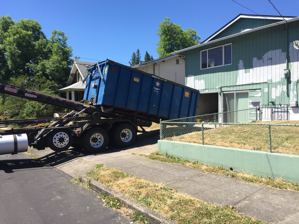 Here's a dump truck being delivered. They charge by the weight. This dump has capacity for 30 yards of waste. 3000 pounds of waste picked will cost ~$500. This is way cheaper and easier than hauling all of this waste to the dump myself.