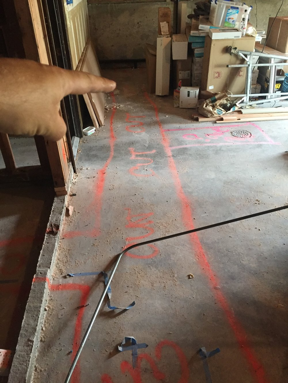 The spray paint marks on the ground are where trenches will need to be cut in order to lay down new ABS drain lines for the bathroom.