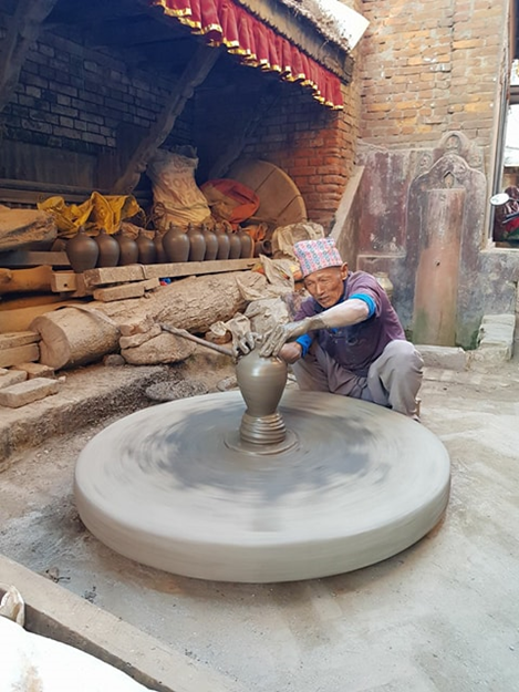 Nepali Man making a piggy-bank out of clay