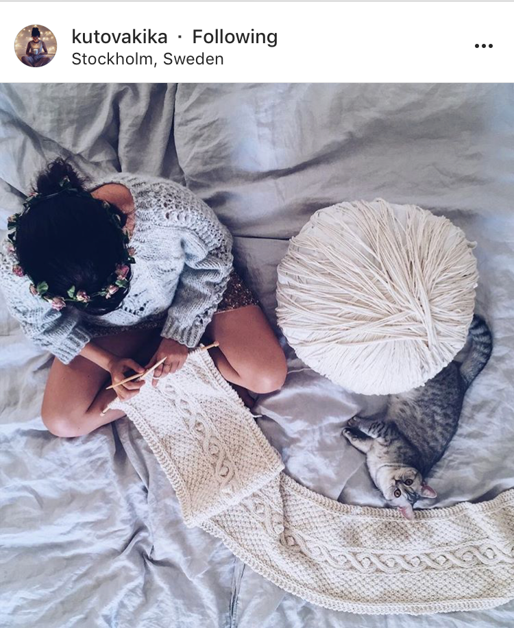 Kika  sat knitting (with a floral crown) with a giant ball of yarn, a fluffy cat, yes please.