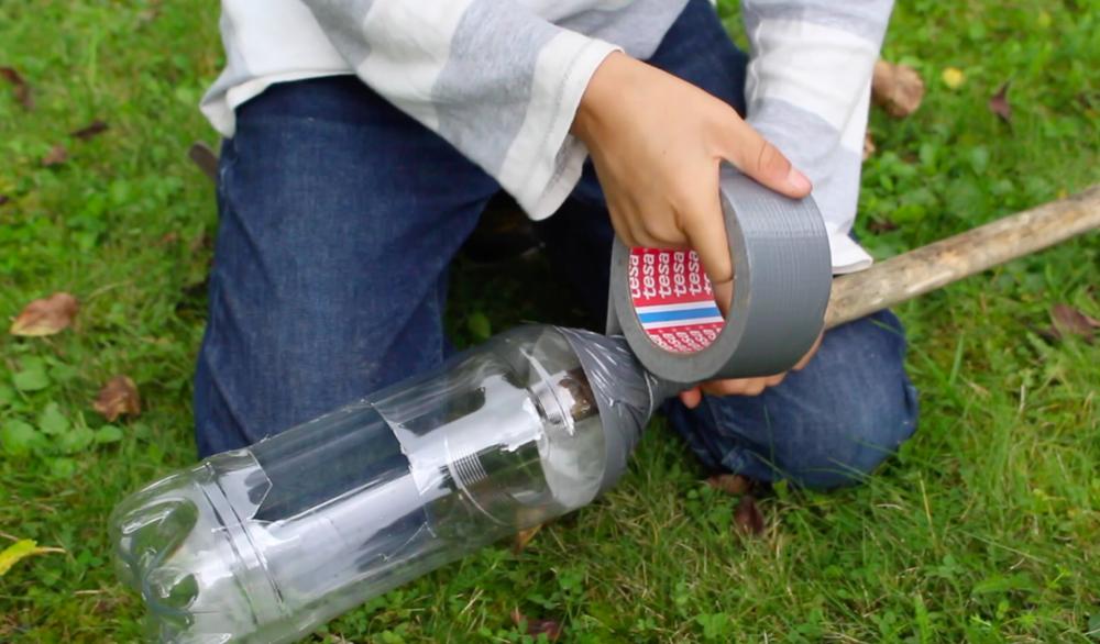 3. Sätt in träskaftet i hålet där flaskhalsen suttit och tejpa fast träskaftet i flaskan med silvertejp.