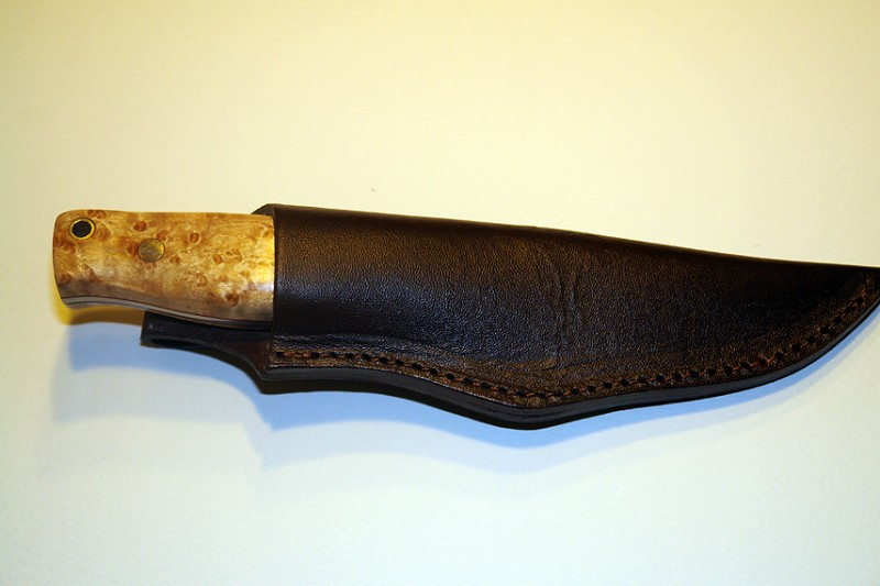 The knife fits snugly in the sheath, and the sheath has a belt loop on the other side.