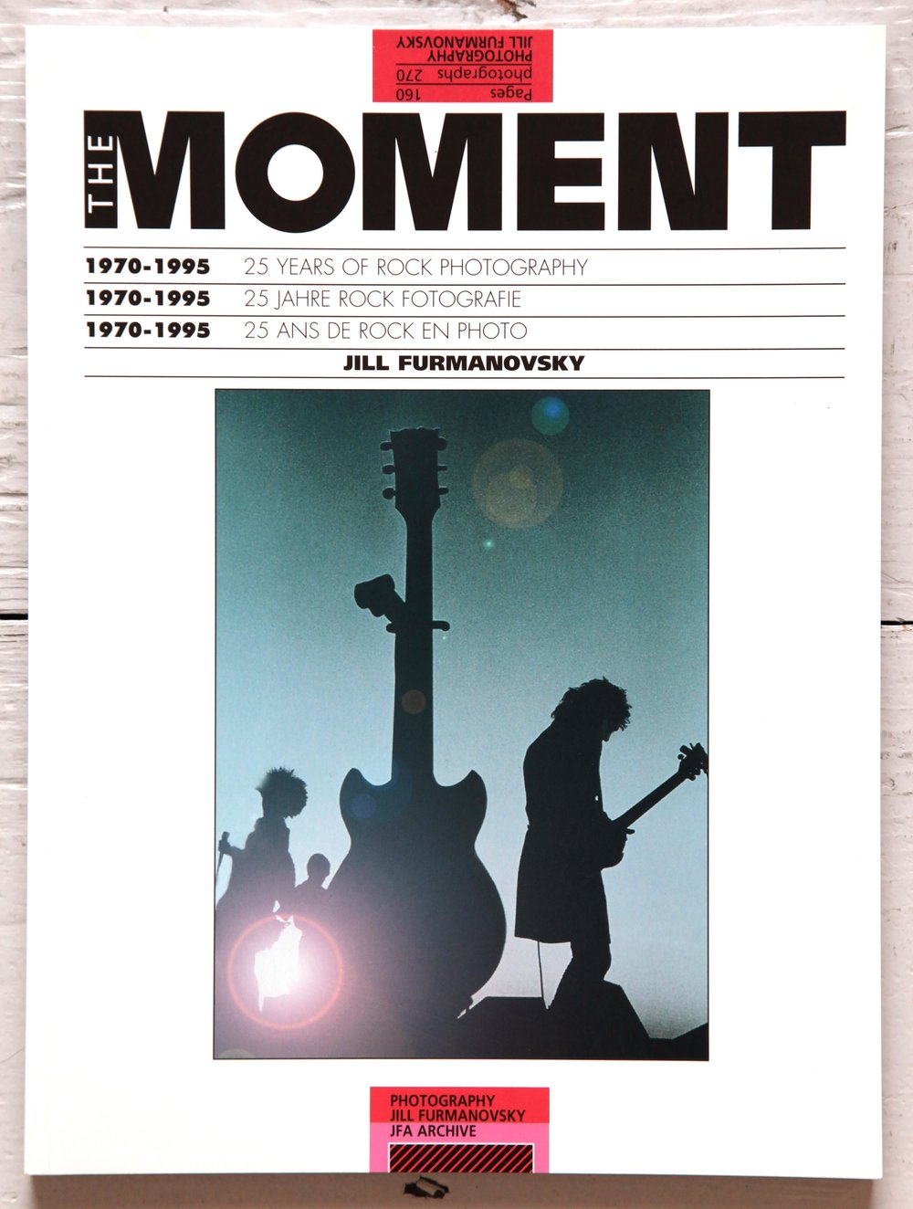 £70 Signed copy of Jill Furmanovsky's 'Moment'. First edition. Published by Dragon's World Ltd, Limpsfield (1995). Soft cover. - An anthology marking the first 25 years of Jill Furmanovsky's illustrious career as one of the world's leading music photographers. Iconic live shots and images taken off-stage of all the greats; from Yes to Oasis, Led Zeppelin to the Sex Pistols, accompanied by personal anecdotes. This signed book is one of the last remaining new copies.