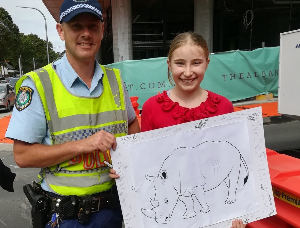 A policeman signed Holly's rhino poster. He told Holly that if people all around the world helped rhinos, it would really make a difference.