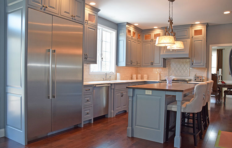 Grey is the New White - Grey is the color of the year for a reason - it is gorgeous!  Raised panels, flush inset refrigerator/freezer, columned legs at island and sink, box feet and lit upper cabinetry make this kitchen one of our most beautiful showpieces. More Pictures