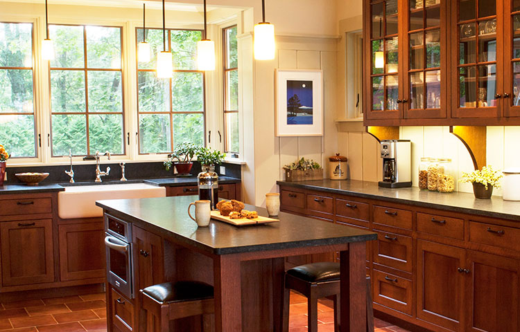Craftsman Kitchen - This elegant kitchen is full of Craftsman details including a custom cut in farmhouse sink, full mullion glass doors in upper cabinetry to highlight homeowner's beautiful glassware and pottery, corbels beneath all the upper cabinetry, and of course the stained quarter sawn oak for the cabinetry.   More Pictures