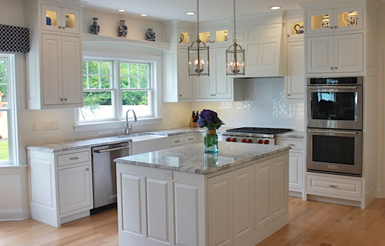 White Shore House Kitchen - Located on Long Island, this kitchen combines crisp white with navy blue to give it a coastal feel. The pure white cabinetry coupled with the glossy white backsplash and lit cabinets to display their navy and white ceramics make this kitchen a showpiece for this coastal home.  More Pictures