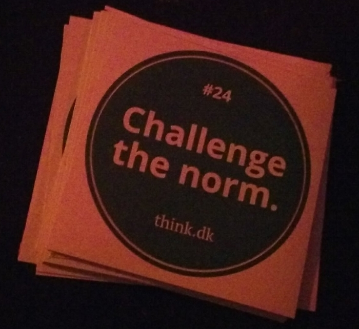 "Another low-fi photo, this one of a think.dk sticker that says ""#24: Challenge the norm""."